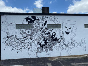 mural being painted on Nice Guys Pizza exterior