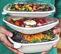 stack of three fiber to-go boxes with food and lids